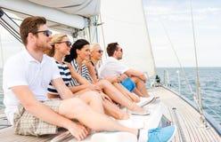 Uśmiechnięci przyjaciele siedzi na jachtu pokładzie zdjęcie royalty free