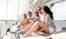 Uśmiechnięci przyjaciele siedzi na jachtu pokładzie Zdjęcia Stock