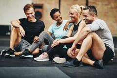 Uśmiechnięci przyjaciele siedzi w gym opowiada wpólnie po exercisi zdjęcie stock