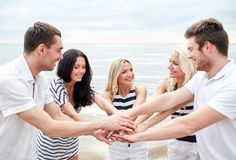 Uśmiechnięci przyjaciele stawia ręki na górze each inny Zdjęcia Royalty Free
