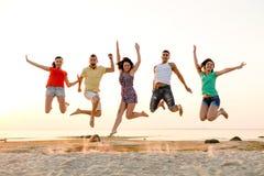 Uśmiechnięci przyjaciele tanczy i skacze na plaży Zdjęcie Royalty Free