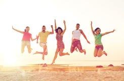 Uśmiechnięci przyjaciele tanczy i skacze na plaży fotografia stock