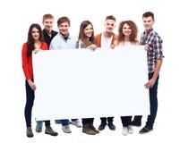 Uśmiechnięci przyjaciele trzyma pustego sztandar zdjęcie royalty free
