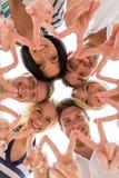 Uśmiechnięci przyjaciele w okręgu Obrazy Royalty Free