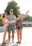 Uśmiechnięci przyjaciele z mapą i miastem prowadzą outdoors fotografia stock