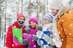 Uśmiechnięci przyjaciele z pastylka komputerem osobistym w zima lesie Fotografia Stock