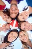 Uśmiechnięci przyjaciele z piłką w okręgu nad niebieskim niebem Fotografia Stock