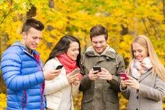 Uśmiechnięci przyjaciele z smartphones w miasto parku Obraz Royalty Free