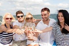 Uśmiechnięci przyjaciele z szkłami szampan na jachcie obraz royalty free