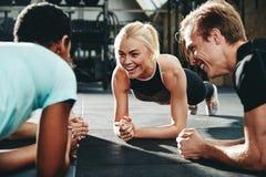 Uśmiechnięci przyjaciele zaszaluje wpólnie podczas gym treningu sesji fotografia royalty free