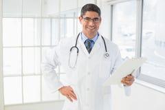 Uśmiechnięci samiec lekarki mienia raporty w szpitalu Obrazy Stock