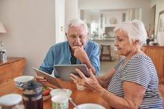 Uśmiechnięci seniory opowiada cyfrowe pastylki nad śniadaniem wpólnie i używa Fotografia Stock