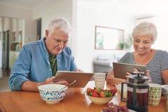 Uśmiechnięci seniory używa cyfrowe pastylki nad śniadaniem w domu Obrazy Stock
