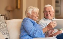 Uśmiechnięci seniory wyszukuje internet od ich żywej izbowej kanapy Zdjęcia Royalty Free