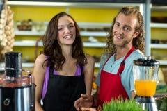 Uśmiechnięci sklepowi asystenci stoi wpólnie w zdrowie sklepu spożywczego sklepie obrazy stock
