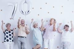 Uśmiechnięci starsi ludzie świętuje z srebnymi balonami zdjęcia royalty free