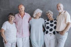 Uśmiechnięci starsi ludzie ma zabawę, stoi przeciw betonowej ścianie obraz stock