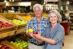 Uśmiechnięci starsi pary mienia jabłka Zdjęcie Royalty Free