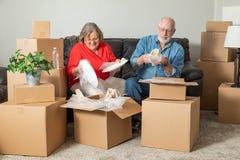 Uśmiechnięci Starszy pary odpakowania lub kocowania chodzenia pudełka zdjęcia stock