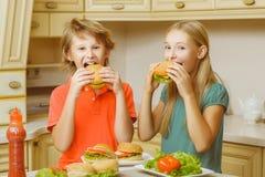 Uśmiechnięci szczęśliwi chłopiec i dziewczyny łasowania hamburgery lub Zdjęcia Stock