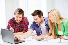 Uśmiechnięci ucznie patrzeje laptop przy szkołą fotografia royalty free