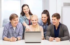 Uśmiechnięci ucznie patrzeje laptop przy szkołą obraz stock
