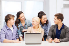 Uśmiechnięci ucznie z laptopem przy szkołą Obrazy Royalty Free