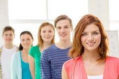 Uśmiechnięci ucznie z nastoletnią dziewczyną w przodzie zdjęcia stock