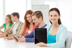 Uśmiechnięci ucznie z pastylka komputerem osobistym przy szkołą obraz stock