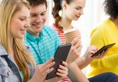 Uśmiechnięci ucznie z pastylka komputerem osobistym przy szkołą Obrazy Stock
