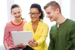 Uśmiechnięci ucznie z pastylka komputerem osobistym przy szkołą Zdjęcie Stock