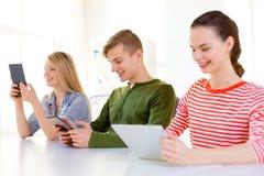 Uśmiechnięci ucznie z pastylka komputerem osobistym przy szkołą Zdjęcia Royalty Free
