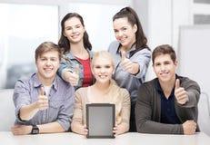 Uśmiechnięci ucznie z pustym pastylka komputeru osobistego ekranem Obrazy Stock