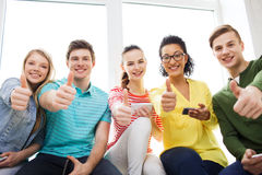 Uśmiechnięci ucznie z smartphone texting przy szkołą Zdjęcie Royalty Free