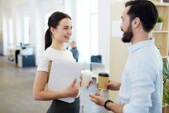 Uśmiechnięci urzędnicy Opowiada na Kawowej przerwie Obraz Royalty Free
