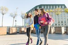 Uśmiechnięci wiek dojrzewania ucznie z plecakami i podręcznikami opowiada naprzód i iść, obraz stock