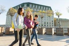Uśmiechnięci wiek dojrzewania ucznie z plecakami i podręcznikami opowiada naprzód i iść, fotografia royalty free