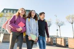 Uśmiechnięci wiek dojrzewania ucznie z plecakami i podręcznikami opowiada naprzód i iść, zdjęcie royalty free