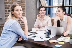 Uśmiechnięci wielokulturowi bizneswomany dyskutuje projekt przy miejscem pracy z laptopem podczas gdy blondynki kobieta patrzeje  Obrazy Royalty Free