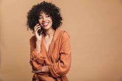 U?miechni?ta ?adna afryka?ska kobieta opowiada smartphone i patrzeje daleko od zdjęcie stock