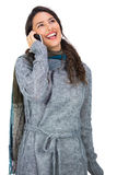 Uśmiechnięta ładna brunetka jest ubranym zim ubrania ma rozmowę telefonicza Obraz Royalty Free