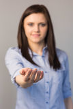 Uśmiechnięta ładna brunetka przedstawia jej pustą rękę Obrazy Stock
