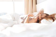 Uśmiechnięta ładna dama kłama w łóżku indoors zamknięte oczy Zdjęcia Royalty Free