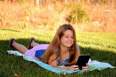 Uśmiechnięta ładna dziewczyna używa jej pastylkę Obrazy Royalty Free