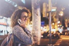 Uśmiechnięta ładna kobieta robi rozmowy wezwaniu z jej przyjaciółmi przez komórka telefonu na ulicie podczas gdy stojący przy noc Zdjęcie Royalty Free