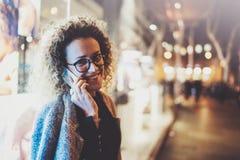 Uśmiechnięta ładna kobieta robi rozmowy wezwaniu z jej przyjaciółmi przez komórka telefonu na ulicie podczas gdy stojący przy noc Zdjęcie Stock