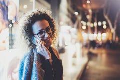 Uśmiechnięta ładna kobieta robi rozmowy wezwaniu z jej przyjaciółmi przez komórka telefonu na ulicie podczas gdy stojący przy noc Obraz Stock