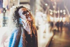 Uśmiechnięta ładna kobieta robi rozmowy wezwaniu z jej przyjaciółmi przez komórka telefonu na ulicie podczas gdy stojący przy noc Fotografia Royalty Free