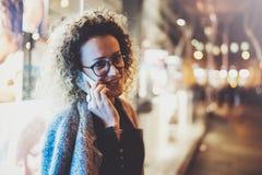 Uśmiechnięta ładna kobieta robi rozmowy wezwaniu z jej przyjaciółmi przez komórka telefonu na ulicie podczas gdy stojący przy noc Obrazy Stock