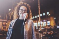Uśmiechnięta ładna kobieta robi rozmowy wezwaniu z jej przyjaciółmi przez komórka telefonu na ulicie podczas gdy stojący przy noc Zdjęcia Royalty Free